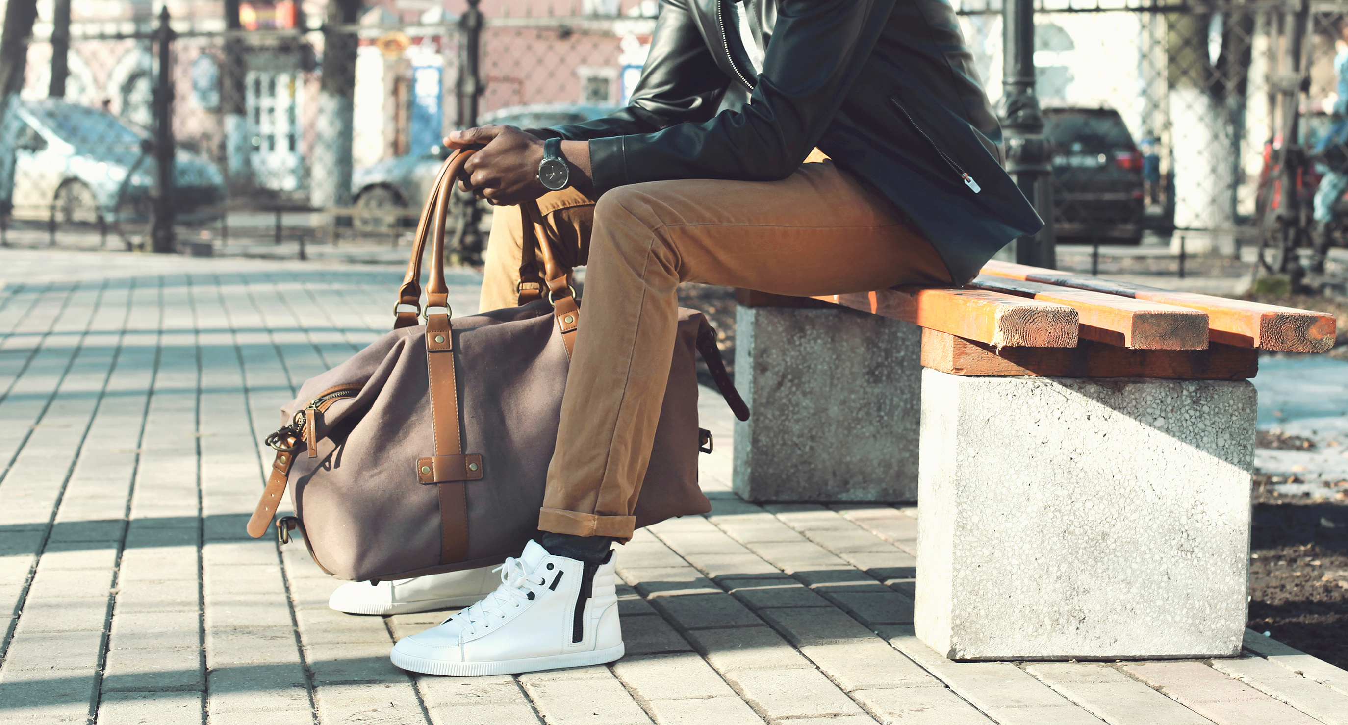 Fashion man with bag sits on a bench in the city close-up